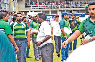 Old boys of Isipathana College attempt to control a boisterous set of supporters who hurled  objects onto the field