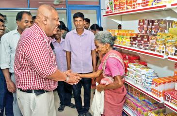 Minister Mangala Samaraweera heartily greets a customer at the Co-op shop  Pix: Rukmal Gamage