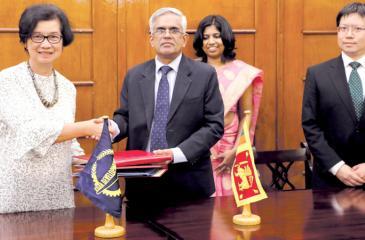 Sri Widowati and Dr. R.H.S. Samaratunga, exchange the agreement. Kuniyoshi Ito is also present.