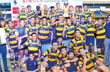The champion Royal College rugby team celebrate with the Singer inter-school League title after beating St. Peter's College 32-13
