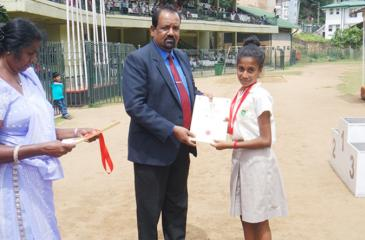 Himansa Herath of Iris House, the Under 14 Champion athlete (girls)- receiving her award from the Chief Guest.