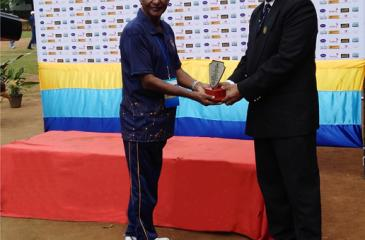 Eric Hulangamuwa being presented with a memento for his services towards hockey by M. Maharoof the Secretary of the Hockey Association of Matale.