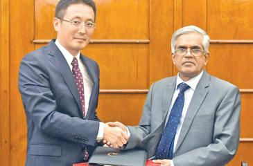 Secretary, Ministry of Finance and Mass Media, R. H. S. Samaratunga exchanges the agreement with JICA chief Tanaka Fusat.