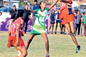 Players from Holy Family Convent Kurunegala (red) and St. Bridget's Convent compete in their Eva netball championship match at the Air Force ground in Colombo yesterday (Pic by Thilak Perera)