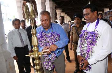 Minister Mangala Samaraweera lights the oil lamp at the opening  of the exhibition.