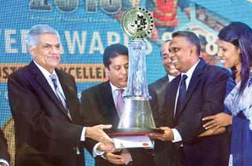 Prime Minister Ranil Wickremesinghe presents the Crystal award to a representatives of Link Natural Products (Pvt) Ltd, winner in the Extra Large Category - National Level manufacturing sector at the CNCI Achiever Awards 2018. Picture Chaminda Niroshana