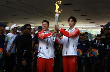 Chinese runners handover the torch during the last torch relay in Jakarta on August 18, 2018, ahead of the opening ceremony of the 2018 Asian Games. (AFP)