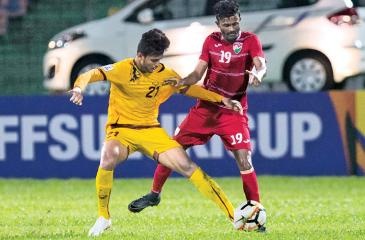 Sri Lanka's Asela Madushan (in yellow) and Mohamed Mujuthaaz from the Maldives compete for the ball