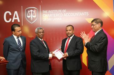 The first copy of the Standard being presented to Minister Bathiudeen by Lasantha Wickremasinghe. Jagath Perera and Sanath Fernando are also in the picture.