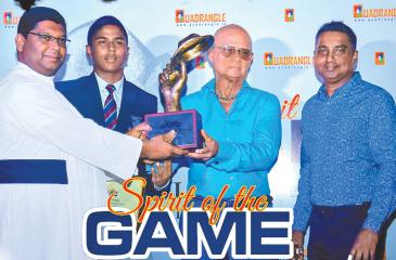 Rev. Fr. Henry Wijeyeratne (left) Principal of St. Anthony's College Kandy receiving the Lorenz Pereira Trophy from Lorenz Pereira himself flanked by Sujith Silva, Editor in Chief of Quadrangle Magazine