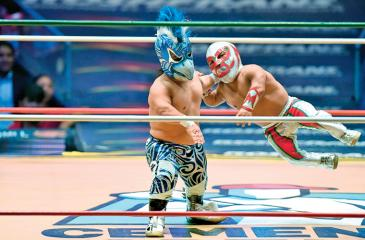 Mexican dwarf fighter Microman (red) struggles with his opponent during a fight at the Arena Mexico (AFP)