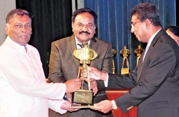 Chairman / Managing Director, Narayanasamy Gokulakrishnan receives the award from Minister Harsha de Silva. Director Sinnathamby Balasundaram looks on.