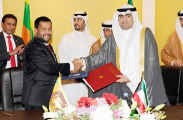 Minister of Industry and Commerce Rishad Bathiudeen (second from left) and Minister of Commerce and Industry of Kuwait Khaled Nasser Al-Roudan (right) exchange documents. Ambassador of Sri Lanka in Kuwait B. Kaandeepan (far left) and Kuwaiti officials (at right) look on.