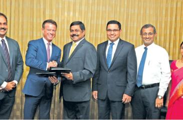 Commercial Bank Managing Director S. Renganathan and RippleNet Senior Vice President – Global Sales, John Mitchell (third and second from left respectively) exchange the agreement. The Bank's Chief Operating Officer Sanath Manatunge (third from right) and representatives of the management of the two institutions look on.