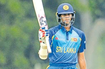 Navod Paranavitharana raises his bat after scoring 50