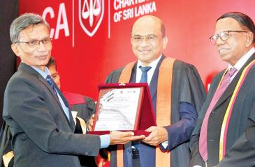A representative from the public sector organisation receiving the award from Auditor General Gamini Wijesinghe. President of APFASL, V. Kanagasabapathy looks on.