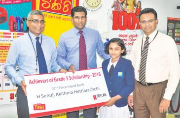 H.A. Senuji Akithma Hettiarachchi receives the cheque from Seylan Bank officials.
