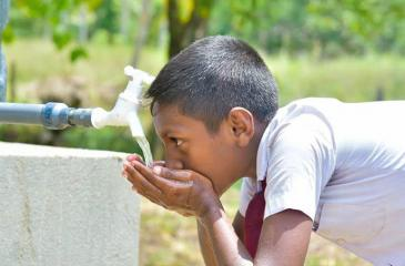 A student of  Medhananda Kanishta Vidyalaya drinks water, after the commissioning of  the treatment plant.