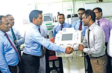 Senior Brand Manager Darshana Appuhami presents the Dialysis machine to Deputy Director Batticaloa Teaching Hospital, Dr. Kulaveerasingam Mohanakumar. Members of Batticaloa Teaching Hospital Dr. S Mathanalagan, Anaesthetist, Dr. P Yoganath, Anaesthetist, C Pushparaja, In Charge SICU, Namonidi, Subject Clerk, David and Amir Ali, Accountants look on.