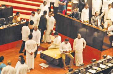 The table on which the highest symbol of respect in Parliament - the Mace, is kept, being thrown to the well of the House and MPs casually seated on the table at the November 16 proceedings that ended abruptly Pic: Hirantha Gunathilaka