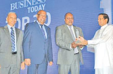 Managing Director and Chief Executive Officer of Ceylinco Insurance Ajith Gunawardena receiving the award from President Maithripala Sirisena. Directors Patrick Alwis Thushara Ranasinghe look on.