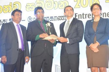 Chairman of Bopitiya Auto Enterprises Jude Rodrigo who was adjudged Best Entrepreneur of the Year receives the award from Chairman, NEDA, Daskshitha Bogollagama. Country Director at WUSC, Esther McIntosh and President, National Chamber of Commerce of Sri Lanka, Sujeewa Samaraweera look on.