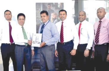 Sanjay Wijeymanne, Deputy General Manager of HNB Retail Banking exchanges the agreement with Sujith Peiris, Director of Strategic Business Development at Hyundai Lanka (Pvt) Ltd. Flanked by Hyundai officials (on left) and HNB Bank officials (right) at the signing of the agreement.