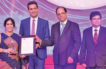 HNB Chief Financial Officer, Anusha Gallage receives the Silver Award in the Banking Institutions category from Chairman of the Annual Report Awards Committee 2018, Heshana Kuruppu. Past President of The Institute of Chartered Accountants of Sri Lanka, Yohan Perera and Secretary of The Institute of Chartered Accountants of Sri Lanka, Prasanna Liyanage look on.