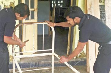 Pan Asia Bank staff' painting a hospital bed.