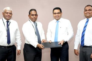Commercial Bank Chief Operating Officer Sanath Manatunge (second from right) and Fairway Holdings Group Chief Executive officer Imal Fonseka exchange the agreement in the presence of Fairway Holdings Chief Information Officer Kumar Melvani (left) and the Bank's Deputy General Manager, Marketing Hasrath Munasinghe.