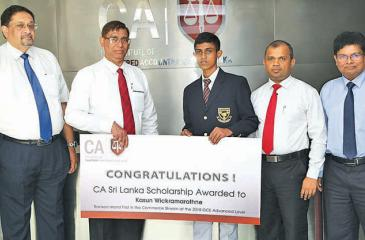 Kasun Wickramarathna of Maliyadeva College, Kurunegala, the first in the island in the commerce stream at the 2018 GCE Advanced Level examination, receives the scholarship from the Institute's President, Jagath Perera. Vice President Manil Jayesinghe, Council Member Sanjaya Bandara and Secretary Prasanna Liyanage look on.
