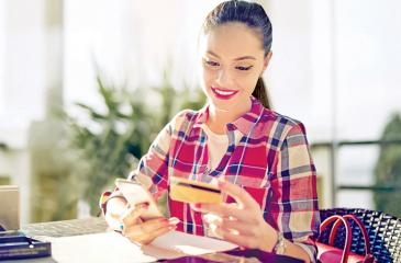 Girl is shopping online using her mobile phone and credit card in a cafe