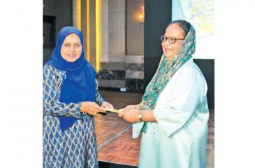 Zarina hands over the first copies of her books to Mrs. Jezima Ismail