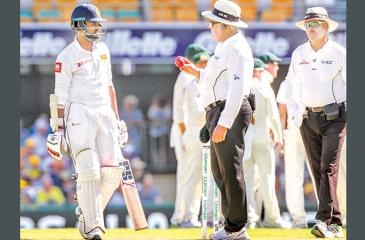 Sri Lanka's Lahiru Thirimanne (L) questions umpire Marais Erasmus after being dismissed by the decision review system (DRS) during the first cricket Test against Australia at the Gabba in Brisbane yesterday. He was out for 32 caught behind off paceman Pat Cummins (AFP)