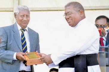 Fr Trevor Martin presents a memento to distinguish old boy of St. Peter's College and former All Ceylon cricketer Dr HIK  Fernando (left)
