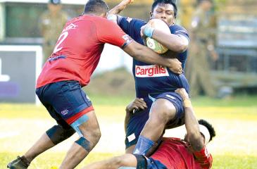 In this file photo Police player Rasith Silva is held by two defenders of CR and FC during their rugby match at Longden Place in Colombo. Police will field a foreign player in their remaining three League matches starting with the first match against Havelocks today at Havelock Park (Picture by Thilak Perera)