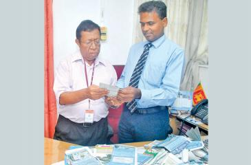 Head of Fund Management D.M. Danasena and Senior Associate Editor Sunday Observer Dudley Jansz selecting the readers' Coupon No.11 winners of the Observer-Mobitel School Cricketer 2019 contest at Lake House (Pic by Siripala Halwala)