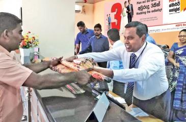 HDFC Bank General Manager and CEO Palitha Gamage presents a gift to a 'Smart Goals' customer.