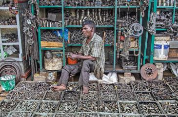 Experienced vendor, P. Kandiah sits on a heap of nuts and bolts laid out in front of him on the pavement of Sangaraja Mawatha