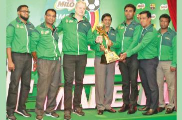 Fabrice Cavallin, (centre) Nestlé Lanka Managing Director, handing over the Milo Football Champions Trophy to Sunil Jayaweera (right), Special Consultant Sports from the Ministry of Education at the launch in the presence of Bandula Egodage, Vice-President Corporate Affairs & Communications at Nestle