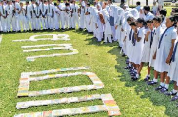 Students standing next to letters in Sinhala, English and Tamil forming the word amma