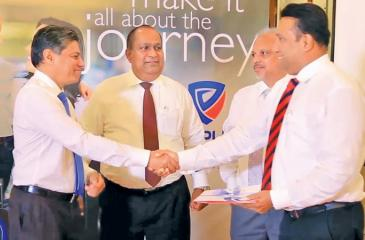 People's Bank CEO/GM N. Vasantha Kumar, People's Leasing & Finance CEO Sabry Ibrahim and People's Insurance CEO  Deepal Abeysekera present the People's Travelsmart Insurance Policy to Finlay's Insurance Broker's CEO Sanjiv Keerthiratne.