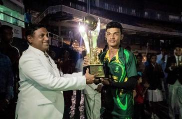 Skipper of Bandaranayake Central College Kalindu Kaudisha receiving the winning trophy from Henegama Central College Principal Vijaya Sathyajeeth Kularatne