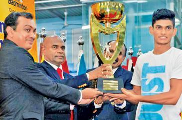 Buwaneka Gunatilleke receiving the men's Open champions trophy from the Army Commander Lt General Mahesh Senanayake at the Defenders Open Badminton at the Army Indoor Stadium Panagoda.
