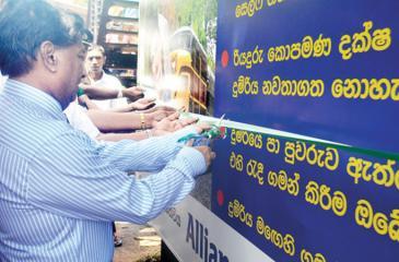 Allianz Lanka officials open a warning sign.
