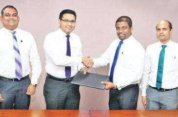 Commercial Bank's Chief Operating Officer Sanath Manatunge (third from left) and Browns Agriculture General Manager Sanjaya Nissanka exchange the agreement. From left:  Commercial Bank's Manager - Retail Lending Department, Chandana Abeysundara, the Bank's Deputy General Manager, Marketing, Hasrath Munasinghe, Browns Agriculture Deputy General Manager Niyas Ahamed and Business Development Manager Chanaka Chandrasekara.