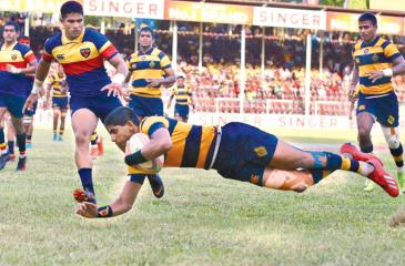 Royal College centre Lehan Gunaratne flies over the line to score a try in their Bradby Shield rugby match against Trinity College at Pallekele yesterday (Picture by Sulochana Gamage)
