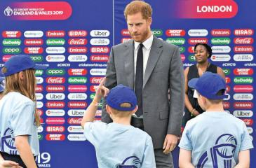 Prince Harry, The Duke of Sussex speaks to the flag bearers as he attends the opening match of the 2019 ICC Cricket World Cup.