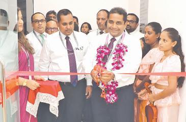 Director/CEO of Seylan Bank, Kapila Ariyaratne opens the branch. Bank officials look on.