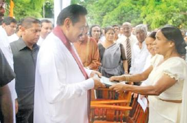 "Nirmala presents her book Premakeerthi to a startled President Rajapaksa saying""The killer of my husband is under your protection."""